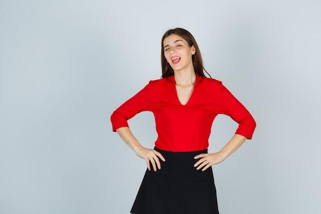 Jonge dame in rode blouse, zwarte rok hand in hand op de heupen