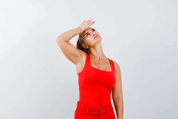 Jonge dame in rood hemd, rode broek die hand op voorhoofd houdt en moe, vooraanzicht kijkt.