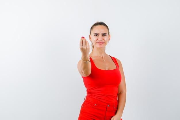 Jonge dame in rood hemd, rode broek die italiaans gebaar toont en ontevreden kijkt, vooraanzicht.