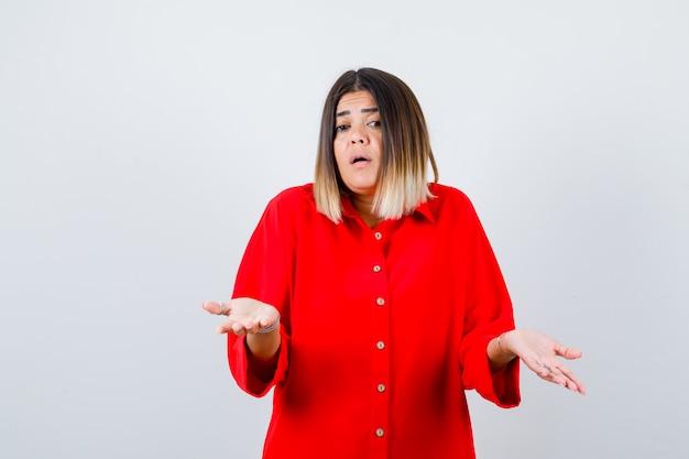 Jonge dame in rood overmaats overhemd die twijfelgebaar toont en perplex kijkt, vooraanzicht.