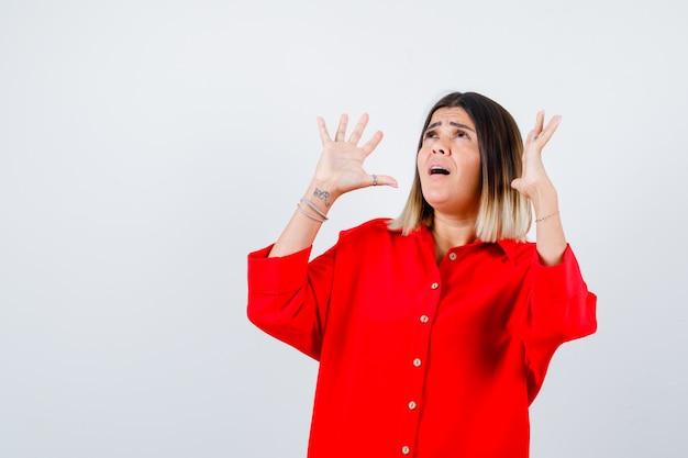 Jonge dame in rood oversized shirt die handen in overgavegebaar houdt en angstig kijkt, vooraanzicht.