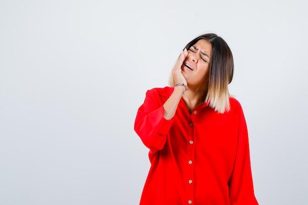Jonge dame in rood oversized shirt die lijdt aan kiespijn en er pijnlijk uitziet, vooraanzicht.