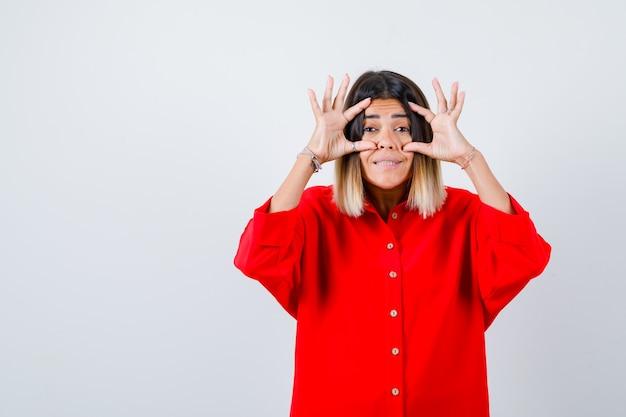 Jonge dame in rood oversized shirt die ogen opent met vingers en er vrolijk uitziet, vooraanzicht.