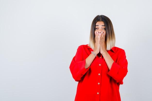 Jonge dame in rood oversized shirt hand in hand op mond en verbaasd kijken, vooraanzicht.