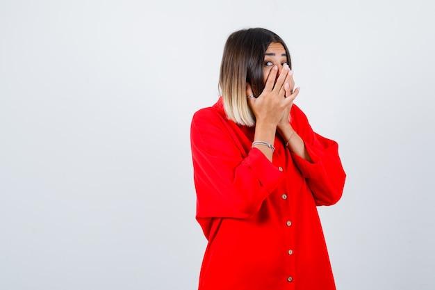Jonge dame in rood oversized shirt met handen op de mond en verbaasd kijkend, vooraanzicht.