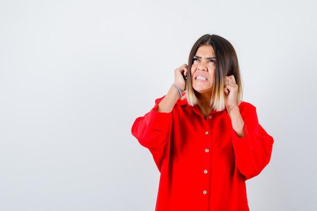 Jonge dame in rood oversized shirt met vuisten in de buurt van gezicht en geïrriteerd, vooraanzicht.