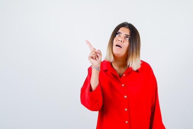 Jonge dame in rood oversized shirt wijzend naar de linkerbovenhoek en perplex kijkend, vooraanzicht.