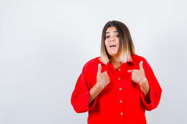 Jonge dame in rood oversized shirt wijzend naar zichzelf als een vraag stellend en opgewonden, vooraanzicht.