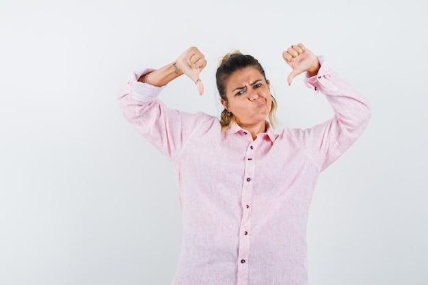 Jonge dame in roze overhemd die dubbele duimen naar beneden toont en ontevreden kijkt