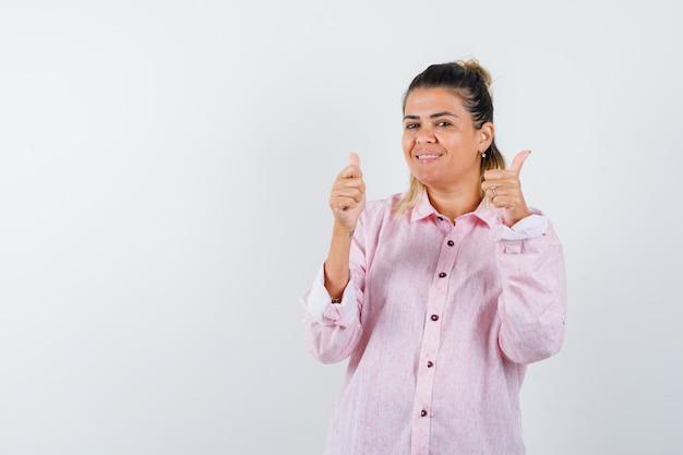 Jonge dame in roze overhemd die dubbele duimen toont en vrolijk kijkt