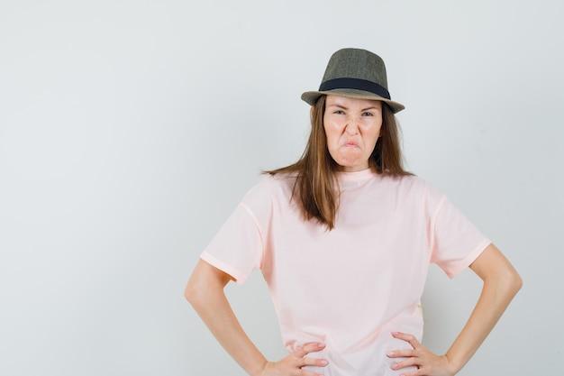Jonge dame in roze t-shirt, hoed hand in hand op taille en op zoek hatelijk, vooraanzicht.