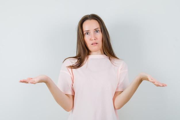 Jonge dame in roze t-shirt met hulpeloos gebaar en op zoek naar verward, vooraanzicht.