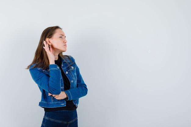 Jonge dame in shirt, jas die een privégesprek afluistert en er nieuwsgierig uitziet, vooraanzicht.