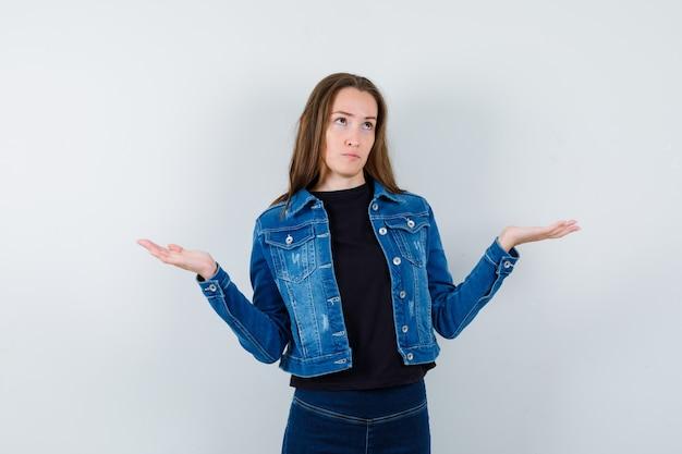 Jonge dame in shirt, jas die een weegschaalgebaar maakt en peinzend kijkt, vooraanzicht.