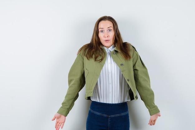Jonge dame in shirt, jas die hulpeloos gebaar toont door haar schouders op te halen en verward te kijken, vooraanzicht.