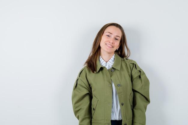 Jonge dame in shirt, jas die naar de camera kijkt en er aantrekkelijk uitziet, vooraanzicht.