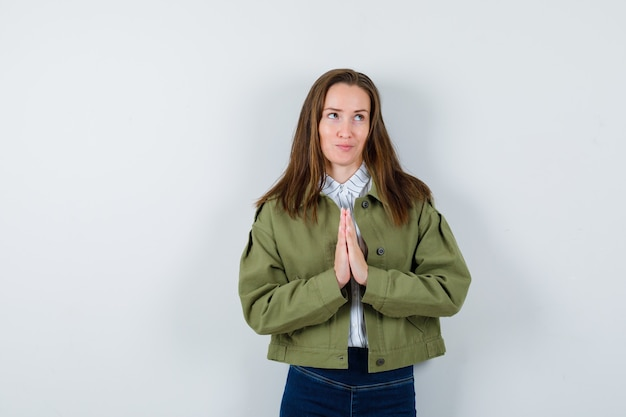 Jonge dame in shirt, jas met namaste gebaar en dromerig, vooraanzicht.