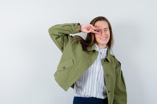 Jonge dame in shirt, jas met v-teken op oog en zelfverzekerd, vooraanzicht.