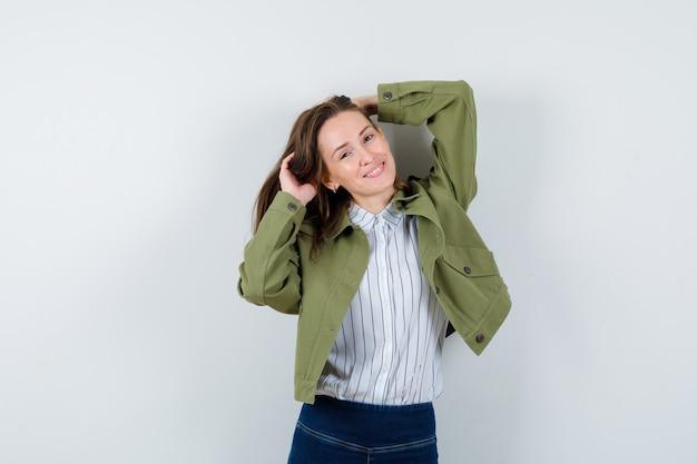 Jonge dame in shirt, jas poseren terwijl ze staan en er glamoureus uitzien, vooraanzicht.