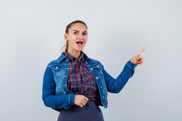Jonge dame in shirt, jas wijzend naar de rechterbovenhoek en verwonderd kijkend, vooraanzicht.