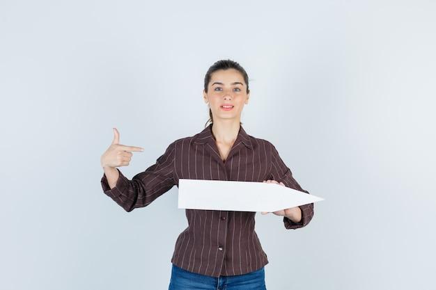 Jonge dame in shirt, jeans wijzend naar de zijkant, papieren poster houdend en weemoedig kijkend, vooraanzicht.