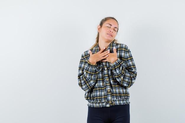 Jonge dame in shirt, korte broek, hand in hand op de borst en op zoek naar dankbaar, vooraanzicht.