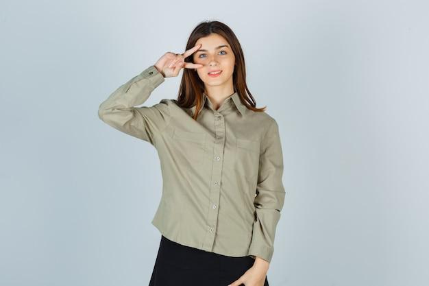 Jonge dame in shirt, rok met v-teken in de buurt van oog en ziet er gelukkig uit, vooraanzicht.