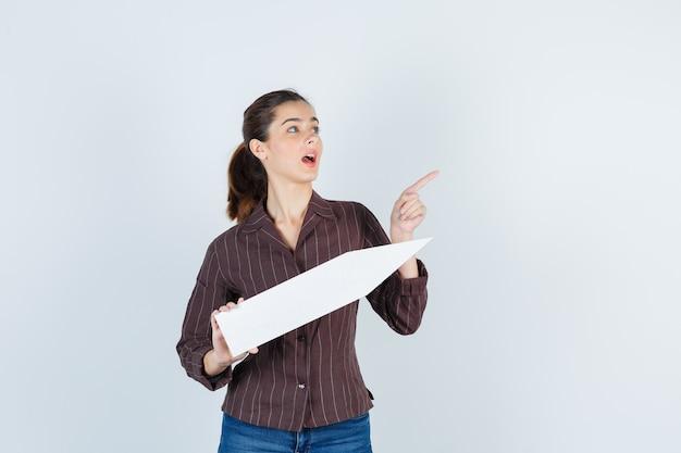 Jonge dame in shirt, spijkerbroek die omhoog wijst, papieren poster bijhoudt en verrast kijkt, vooraanzicht.