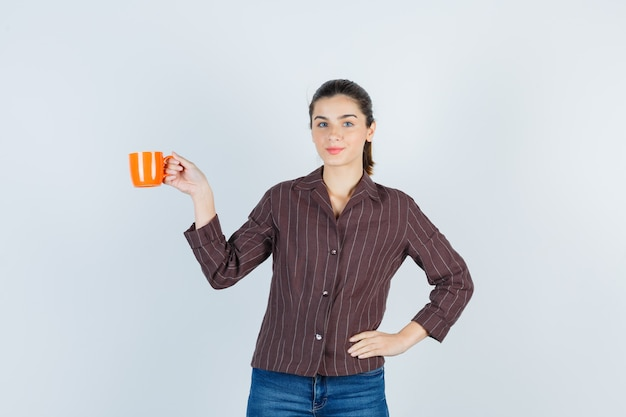 Jonge dame in shirt, spijkerbroek met kop, met hand op taille en schattig, vooraanzicht.