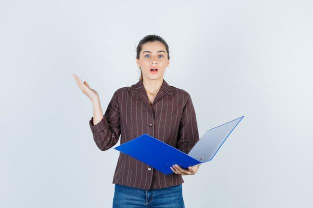 Jonge dame in shirt, spijkerbroek met map, handpalm spreidend en verbaasd kijkend, vooraanzicht.
