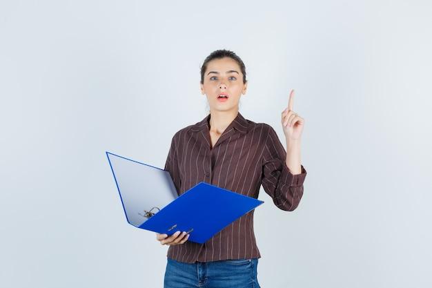 Jonge dame in shirt, spijkerbroek met map, omhoog wijzend en weemoedig kijkend, vooraanzicht.