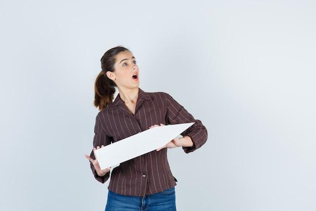 Jonge dame in shirt, spijkerbroek met papieren poster, opkijkend en geschokt, vooraanzicht.