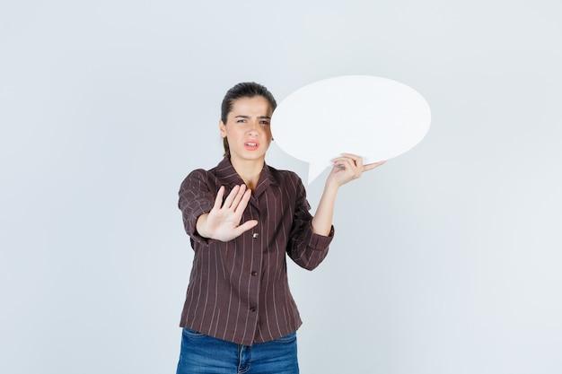 Jonge dame in shirt, spijkerbroek met stopgebaar, papieren poster bijgehouden en teleurgesteld, vooraanzicht.