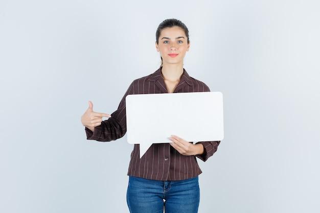 Jonge dame in shirt, spijkerbroek wijzend naar de zijkant, papieren poster houdend en tevreden kijkend, vooraanzicht.