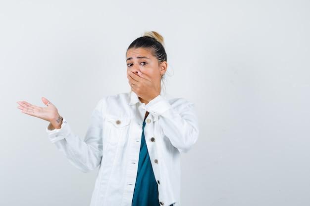 Jonge dame in shirt, witte jas met hand op mond, doet alsof ze iets laat zien en ziet er bang uit, vooraanzicht.