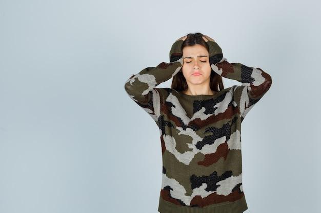 Jonge dame in sweater die hoofd met handen omklemt en droevig kijkt