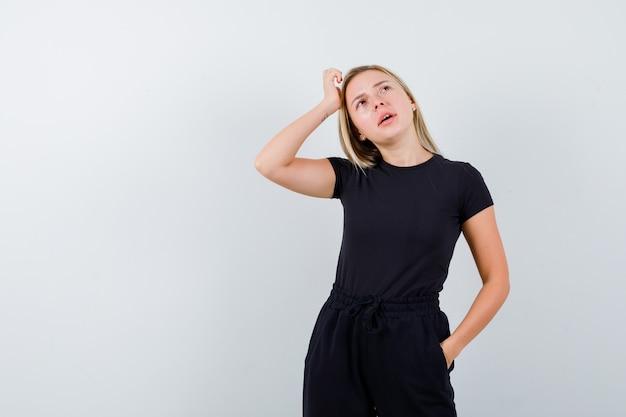 Jonge dame in t-shirt, broek die hand op hoofd houdt en nadenkend, vooraanzicht kijkt.