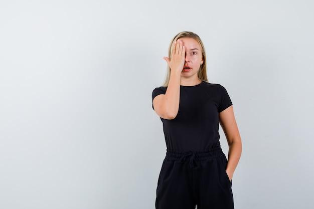 Jonge dame in t-shirt, broek die oog bedekt met hand en verbaasd kijkt, vooraanzicht.
