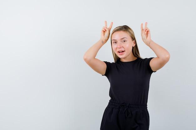 Jonge dame in t-shirt, broek die overwinningsteken toont en gelukkig, vooraanzicht kijkt.