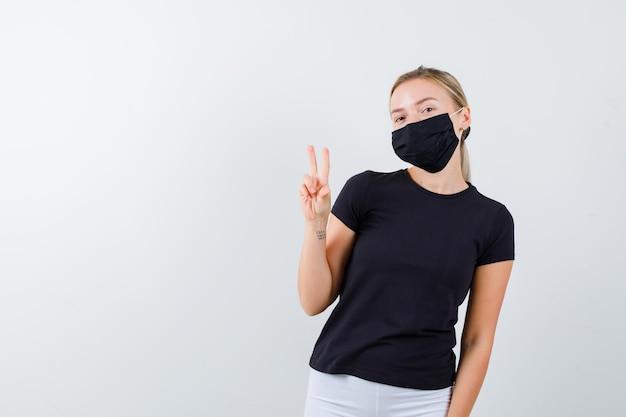 Jonge dame in t-shirt, broek, medisch masker dat overwinningsteken toont en er gelukkig uitziet