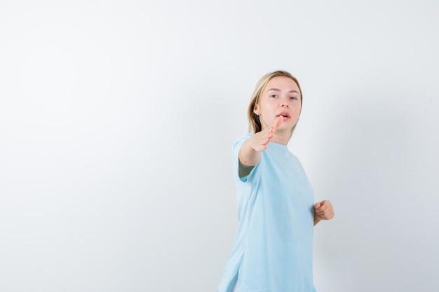 Jonge dame in t-shirt die de hand uitrekt voor begroeting en er zelfverzekerd geïsoleerd uitziet