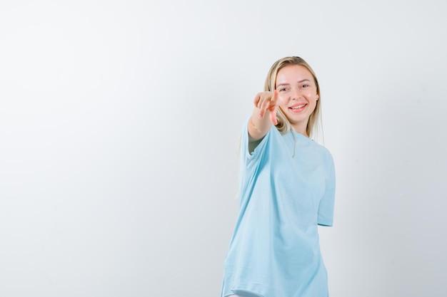 Jonge dame in t-shirt die naar de camera wijst en er gelukkig geïsoleerd uitziet