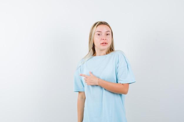 Jonge dame in t-shirt die naar de linkerkant wijst en er zelfverzekerd uitziet, vooraanzicht.