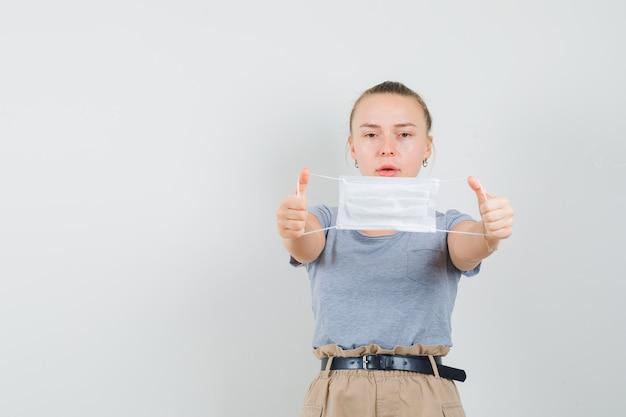 Jonge dame in t-shirt en broek die medisch masker toont en voorzichtig kijkt