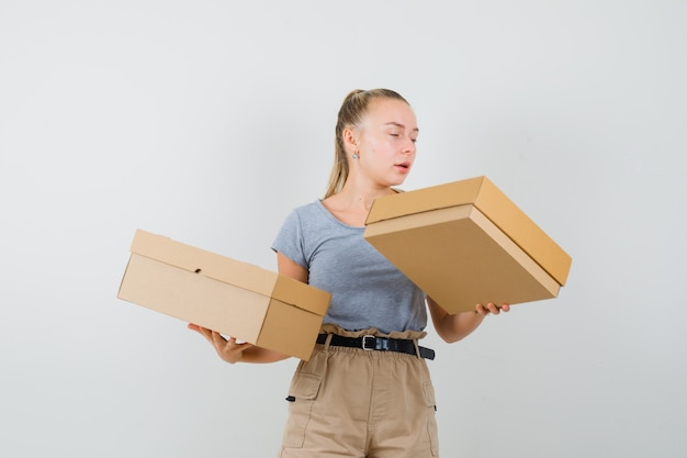 Jonge dame in t-shirt en broek met kartonnen dozen en gefocust op zoek