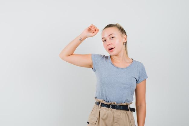 Jonge dame in t-shirt en broek poseren terwijl het verhogen van de arm en er elegant uitziet