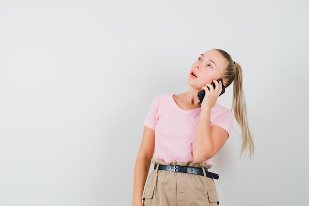 Jonge dame in t-shirt en broek praten op mobiele telefoon en besluiteloos op zoek