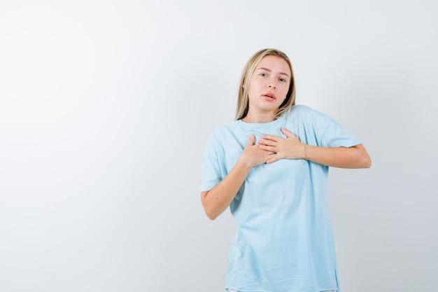 Jonge dame in t-shirt hand in hand op de borst om te bidden en er hoopvol geïsoleerd uit te zien