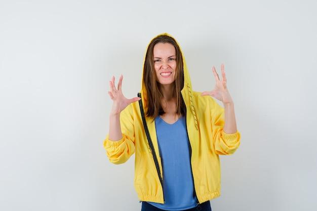 Jonge dame in t-shirt, jas die handen op een agressieve manier opheft en er opgewonden uitziet, vooraanzicht.