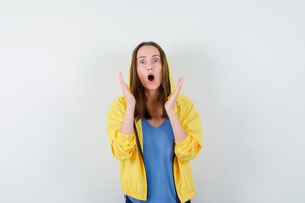 Jonge dame in t-shirt, jas die handen opheft, mond opent en geschokt kijkt, vooraanzicht.